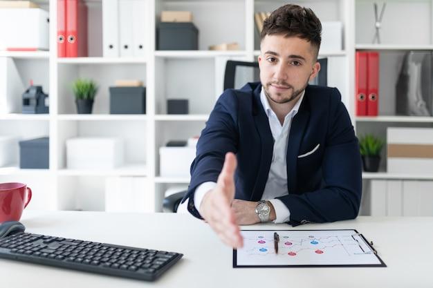 コンピューターテーブルのオフィスに座っている若い男が右手を伸ばします。