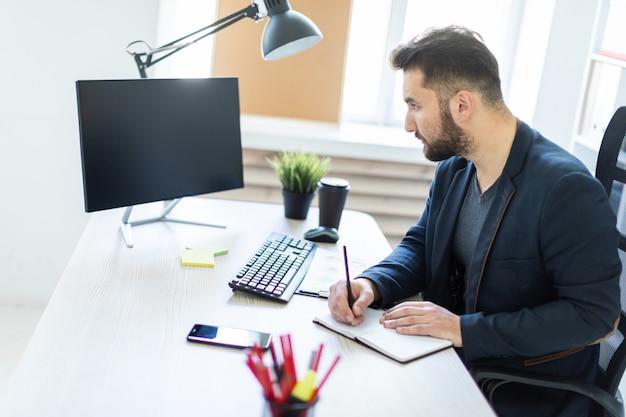 若い男は、ドキュメント、図表、電話を備えたコンピューターデスクのオフィスで働いています。