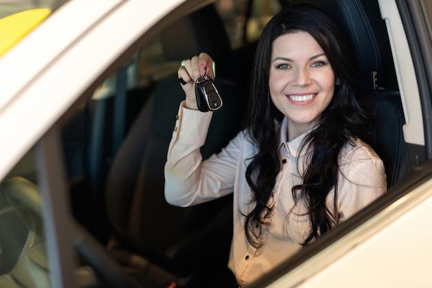 Счастливый клиент женщина покупает новый автомобиль в автосалоне