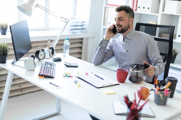 オフィスの若い男がテーブルに座って、電話で話し、コーヒーポットを保持しています。