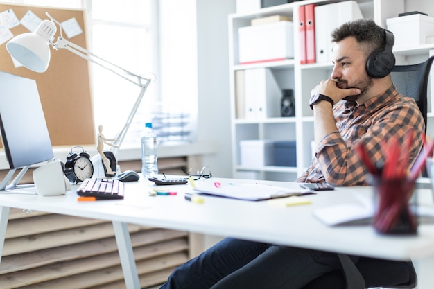 ヘッドフォンの若い男がオフィスのテーブルに座って、モニターを見ています。