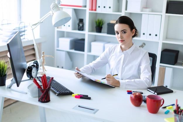 若い女の子がオフィスに座って、ペンを手に持ち、文書を調べます。