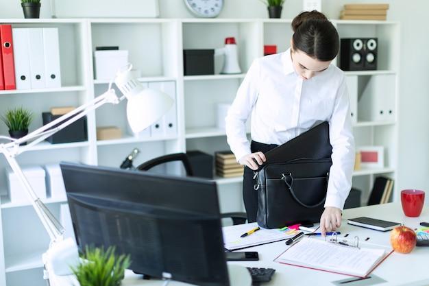 Молодая девушка в кабинете стоит возле стола и складывает вещи в сумку.