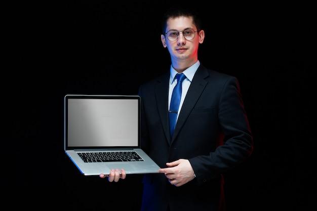 Уверенно красивый стильный бизнесмен держит ноутбук в руках