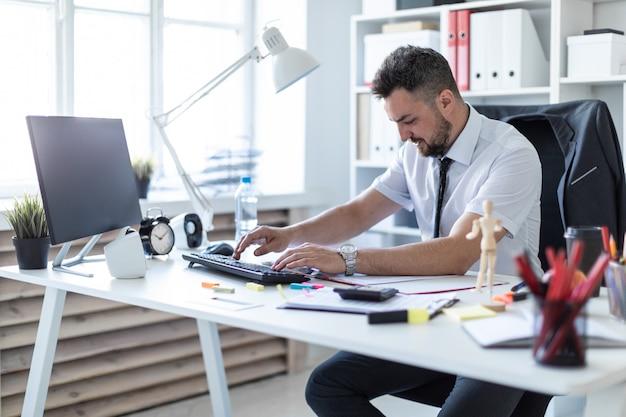 男はオフィスのテーブルに座って、ドキュメントとコンピューターで作業しています。