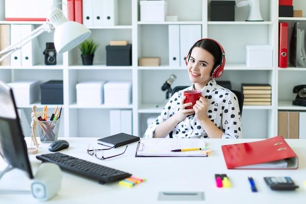Молодая девушка сидит в наушниках за столом в кабинете, держит в руках красную чашку и улыбается.