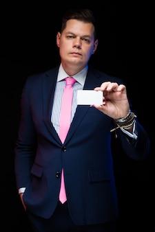ポケットに手で彼の手で名刺を保持している自信を持ってハンサムな実業家