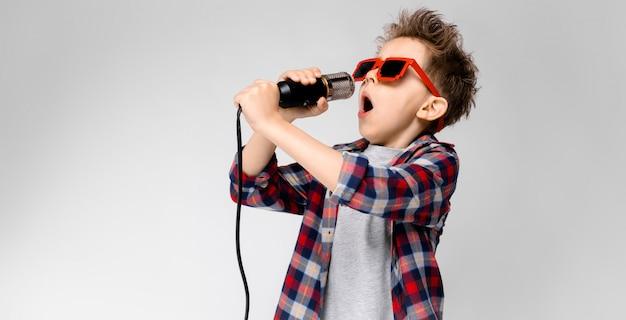 Стоит красивый мальчик в клетчатой рубашке, серой рубашке и джинсах