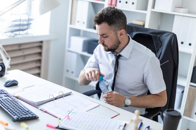 男がオフィスのテーブルに座って、ドキュメントを操作し、水のボトルを開けています。