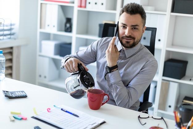 オフィスの若い男がテーブルに座って、電話で話し、コーヒーをカップに注ぎます。