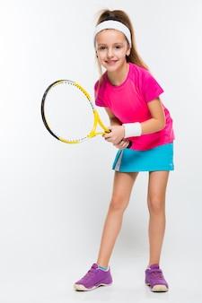 Милая маленькая девочка с теннисной ракеткой в руках