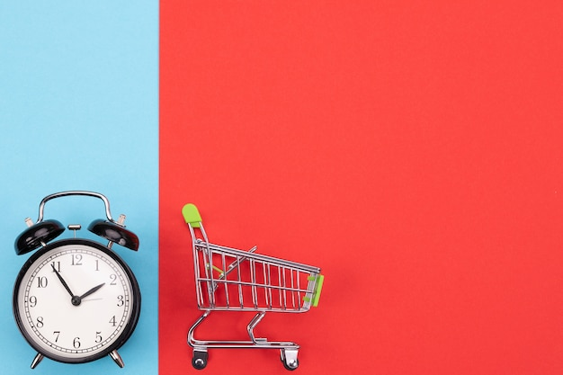 緑のハンドルと時計が付いているスーパーマーケットのカート