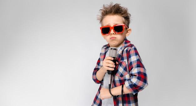 格子縞のシャツ、グレーのシャツ、ジーンズのハンサムな男の子