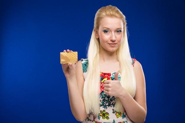 Молодая девушка с кредитной картой в руках