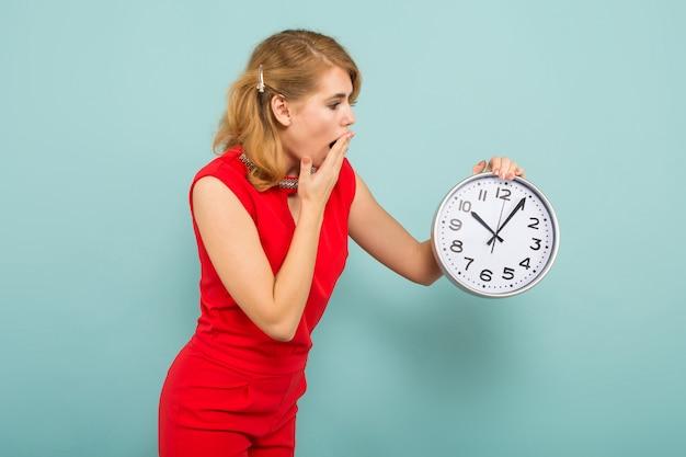 時計と魅力的なショックを受けた女性