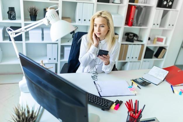 Молодая девушка в офисе сидит за столом с телефоном в руке и разговаривает по нему через гарнитуру.