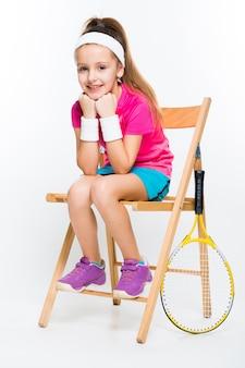 Милая маленькая девочка с теннисной ракеткой на белом