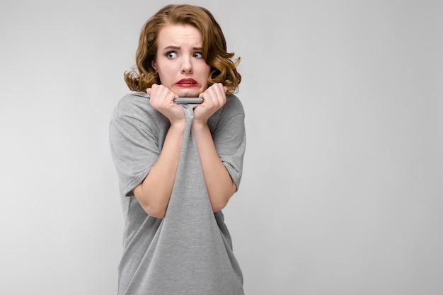 Очаровательная испуганная девушка в серой футболке
