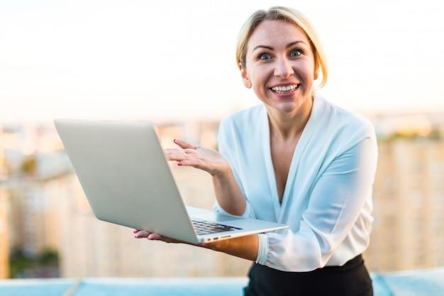 美しいスマートビジネス女性が手にラップトップで屋根の上に立つ