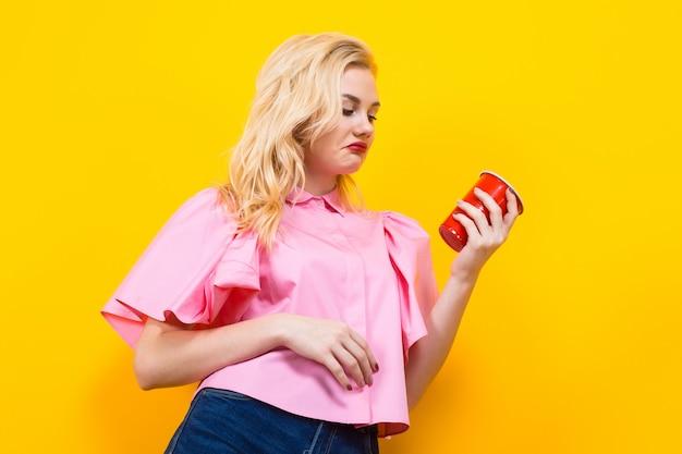 赤カップとピンクのブラウスで金髪の女性