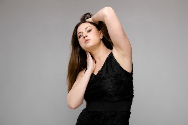 灰色の背景に彼女のセクシュアリティを示すスタジオで感情的な自信を持ってプラスサイズモデル立って