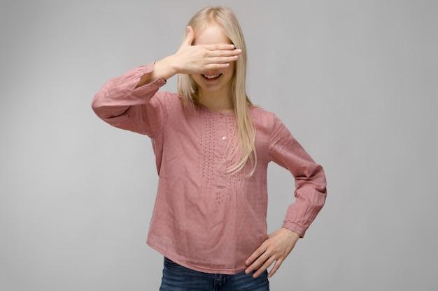 Портрет привлекательной сладкой очаровательной белокурой девочки-подростка в очках в розовой блузке, закрывающей глаза рукой на сером фоне