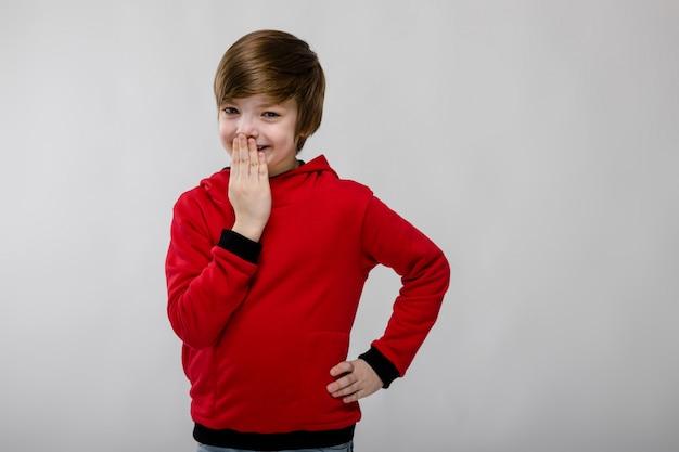 Милый любопытный хитрый маленький кавказский мальчик в красном свитере закрывает рот рукой на сером фоне