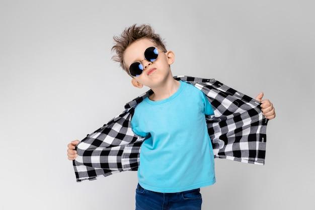 格子縞のシャツ、青いシャツ、ジーンズでハンサムな男の子は灰色の背景に立っています。少年は丸眼鏡をかけています。少年は微笑んでシャツを引っ張ります