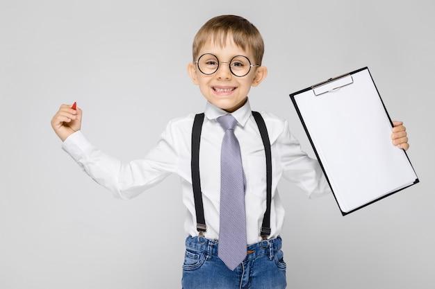 白いシャツ、サスペンダー、ネクタイ、軽いジーンズを着た魅力的な少年が灰色の背景に立っています。少年はペンとメモ用のシートを持っています