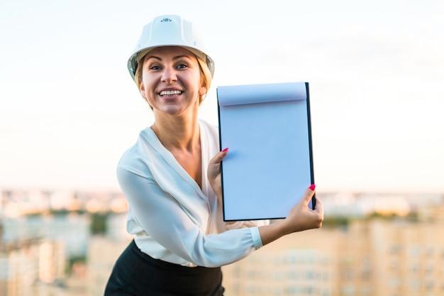 ヘルメットでかなり若い職長が手でタブレットで屋根の上に立つ