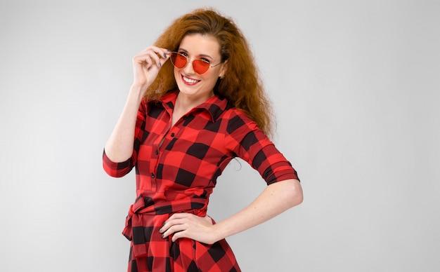 赤い格子縞のシャツの若い赤い髪の少女。赤いメガネの少女。