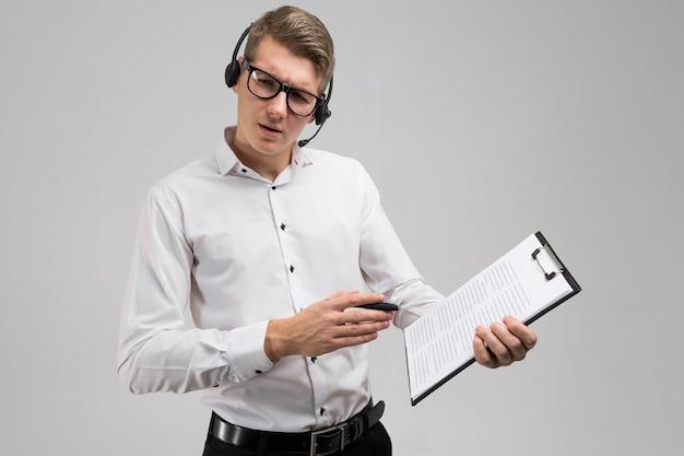 メガネと白い背景で隔離の手で保険付きのヘッドフォンで若い男