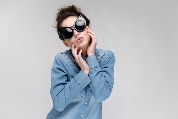 黒眼鏡の若いブルネットの少女。猫メガネ。髪はパンに集められます。女の子は彼女の顔を保持しています。