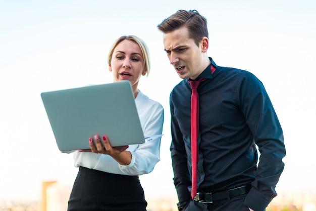 ビジネスマン、若いブルネットの男、若い美しさの金髪女性のカップルが屋根の上に立ち、ラップトップで見る