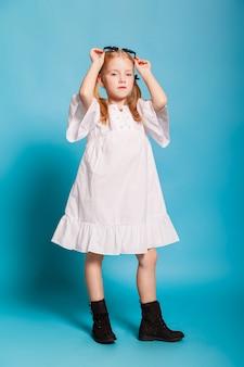 Маленькая девочка с хвостами в стильной одежде и солнцезащитные очки на синем фоне