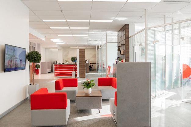 Уголок современного офиса с белыми стенами, серым полом, открытой площадкой с красными и белыми креслами и комнатами за стеклянной стеной