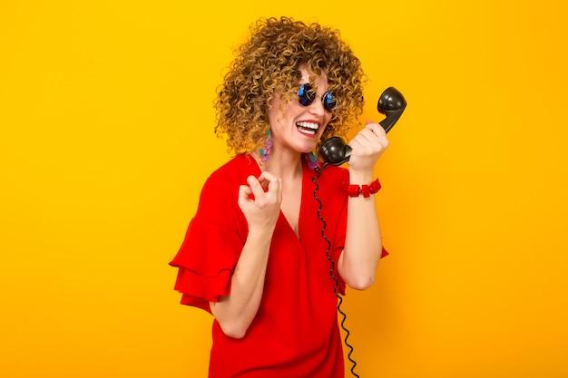 Привлекательная женщина с короткими вьющимися волосами с телефоном