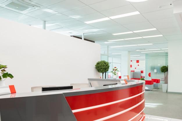赤と白のインテリアを持つ近代的なオフィスの訪問者のためのレセプションエリア