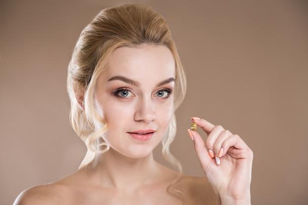 Желтая таблетка в руках женщины