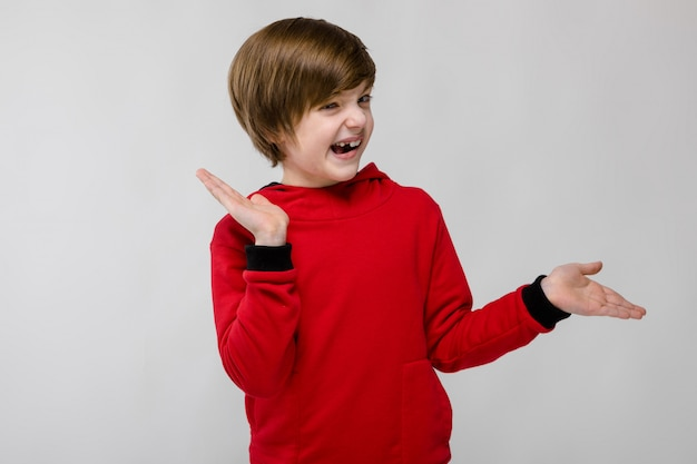 Милый уверенно кавказский маленький счастливый улыбающийся мальчик в красном свитере на сером фоне