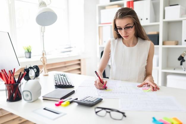 Красивая молодая девушка сидит за столом в офисе, держит ручку в руке и заполняет документы.