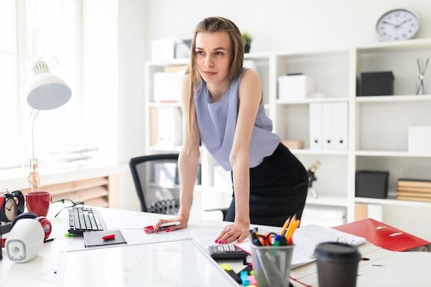 Красивая молодая девушка в офисе стоит рядом опирается на руки и держит розовый маркер.