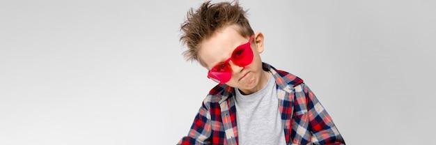 Красивый мальчик в клетчатой рубашке, серой рубашке и джинсах стоит на сером фоне. мальчик в красных очках. мальчик вытягивает руки вперед.