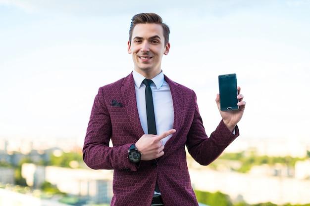 赤いスーツとネクタイとシャツの若い真面目な実業家は屋根の上に立ち、空の電話を表示