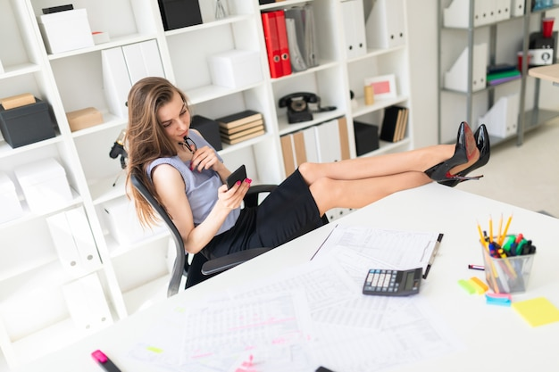 オフィスの美しい少女が足をテーブルに置き、眼鏡と電話を持っています。