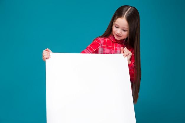 黒髪と市松模様のシャツでかわいい女の子はクリア紙を保持します。