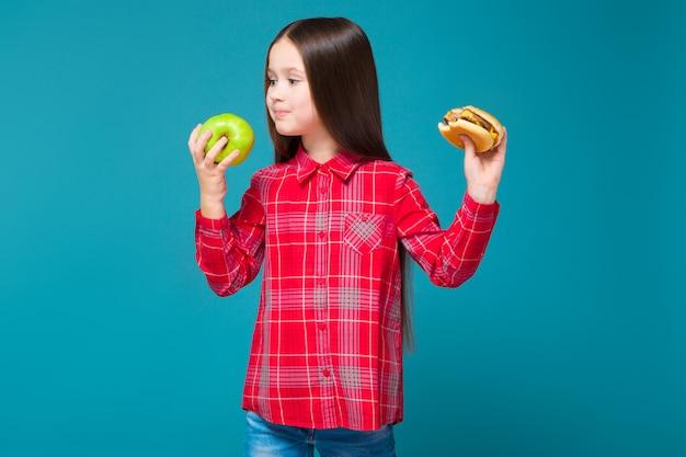 黒髪の市松模様のシャツを着たかわいい女の子がハンバーガーを保持