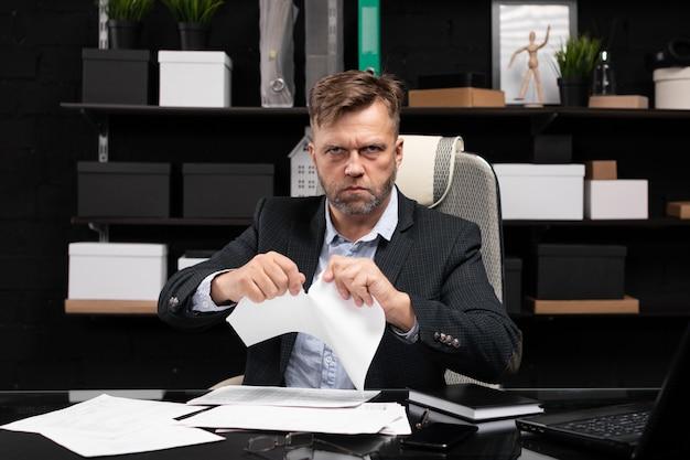 コンピューターのテーブルと涙のドキュメントに座っているビジネスマン