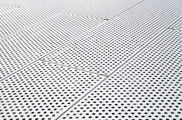 Металлические решетки с множеством круглых отверстий на фоне потолка, перфорированная панель. точечный рисунок на поверхности, диагональный вид.
