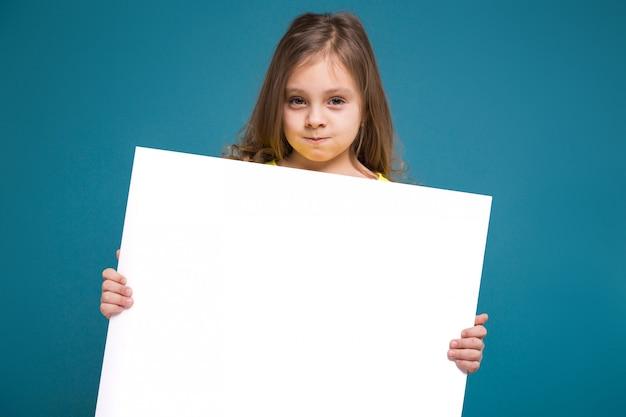 茶色の髪のティーシャツでかわいい女の子はきれいなプラカードを保持します。